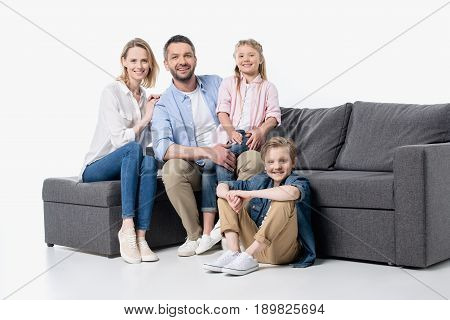 Happy Young Family With Two Children Sitting Together On Couch Isolated On White