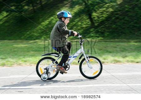 Junge Reiten Fahrrad in einen Helm