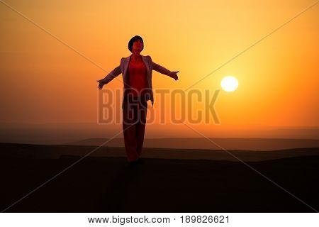Young woman embrace nature on outdoor sunrise background.