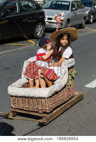 ESTREITO DE CAMARA DE LOBOS PORTUGAL - SEPTEMBER 10 2016: Two children wearing in traditional costumes at Madeira Wine Festival in Estreito de Camara de Lobos Madeira Portugal. The Madeira Wine Festival honors the grape harvest with a celebration of tradi