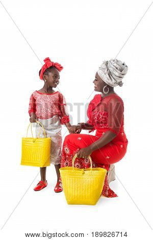 Beautiful African woman and lovely little girl in traditional red clothing with bright yellow wicker tote bags. Isolated on the white studio background