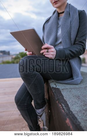 Young girl with tablet working on cloudy sky background. Smart woman sitting on the building's roof in city during work. Blogger, distant work, wireless internet concept