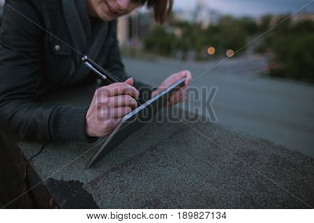 Designer drawing on digital tablet on blurred city background. Creative woman lying on the building's roof during work. Distant work, wireless internet , art profession concept