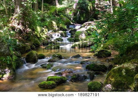 mountain stream with blurred motion of waterfall in beautiful landscape