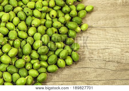 A lot green young walnuts in husks on wooden table