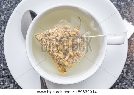 The aroma chamomile tea bag floating on white teacup ready to served in afternoon tea.