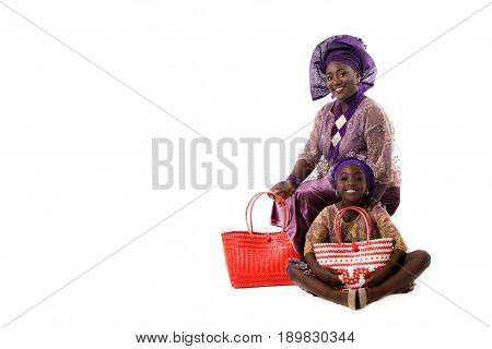 Beautiful African woman and happy little girl sitting on the floor in traditional purple clothing with red wicker tote bags. Isolated on the white studio background.Copyspace