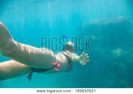 Female apnea swims in tropical sea with american flag bikini. Underwater background of a woman snorkeling and doing skin diving. Watersport activity in Hawaii. Tropical destination holiday concept.