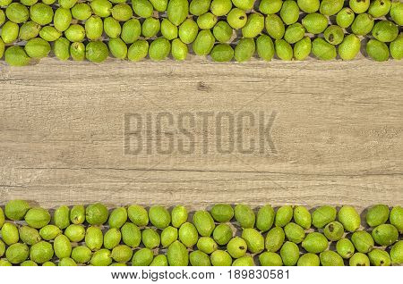 Green young walnuts in husks in row on wooden table