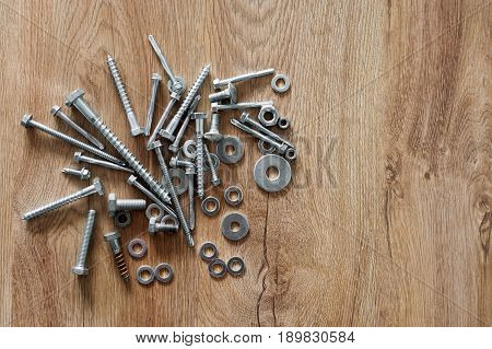Construction tools. The screws, nuts and bolts on wooden background. Repair, home improvement concept. Free space for text, top view, flat lay