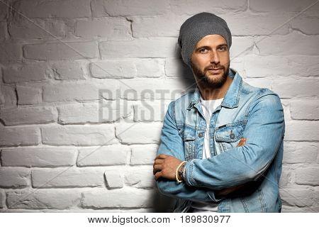 Trendy man in woolly hat standing against white brick wall. Copyspace.