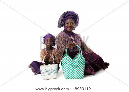 Beautiful African woman and lovely  little girl in traditional purple clothing with wicker tote bags sitting on the floor. Isolated on the white studio background