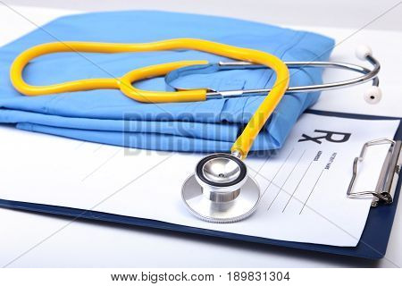 Medical stethoscope, Gloves, RX prescription on blue doctor uniform closeup. Medical tools and instruments shop, therapeutist workspace, physical, blood pressure measurement concept.