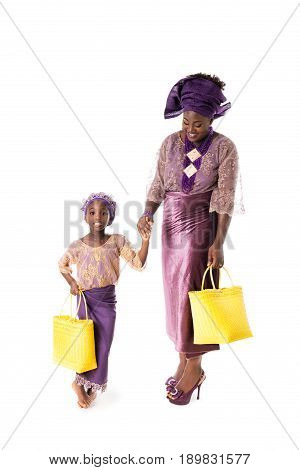 Beautiful African woman and lovely little girl in traditional purple clothing with yellow wicker tote bags. Isolated on the white studio background