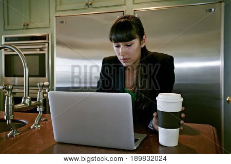 Mixed race businesswoman using laptop in kitchen