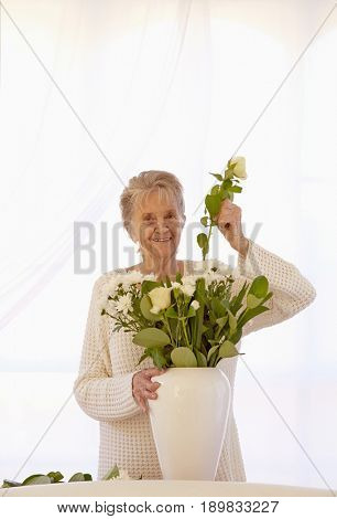 Older Caucasian woman arranging flowers