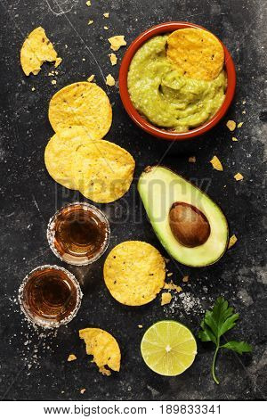 Bowl of mexican nachos chips with homemade fresh guacamole sauce and tequila shots over old  background. Top view. With space for text