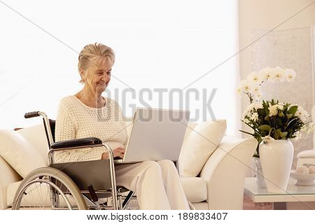 Older Caucasian woman in wheelchair using laptop