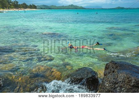 Woman snorkelling over coral reef in kailua beach, east shore in Oahu island, Hawaii, USA. Female bikini snorkeler swims in tropical sea. Watersport activity in Hawaii. Tropical destination holidays.