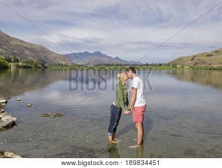 Caucasian couple kissing in rural lake