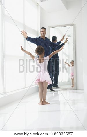 Mixed race father and daughter dancing