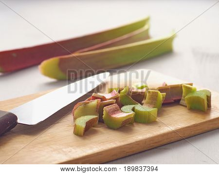 Cooking process. Cutting fresh rhubarb on wooden board. Home baking concept. Cooking ingredients for rhubarb cake. Selective focus.