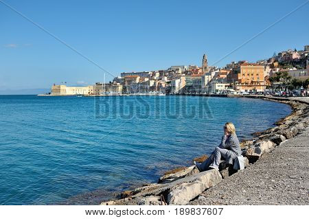 Blond woman relaxes on the seafront of Gaeta Lazio Italy