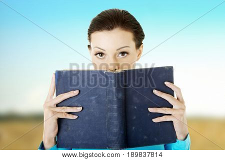 Beautiful young student holding a book on her face.