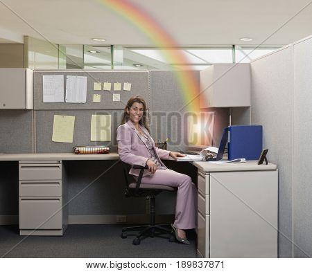 Rainbow erupting from Hispanic businesswoman's computer