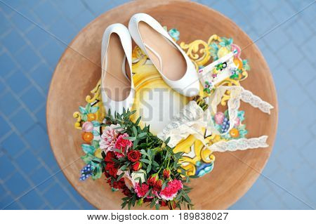 Bridal bouquet and white shoes on a wooden table in wedding day