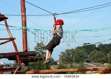 Porträt der jungen Helm tragen und Klettern. Kind in einem hölzernen Abstacle-Kurs in Abenteuer-pl