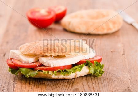 Puccia bread with mozzarella and tomato on cuttingoboard.