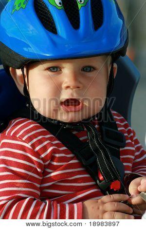 Happy Baby in Fahrrad-Lehrstuhl. 10 Monate alten Baby Boy im Helm.