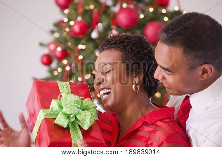 Black couple kissing by Christmas tree