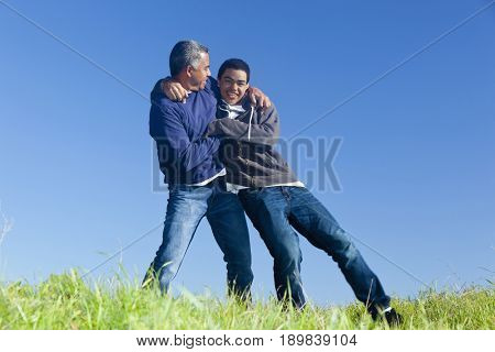 Hispanic father and son playing in park