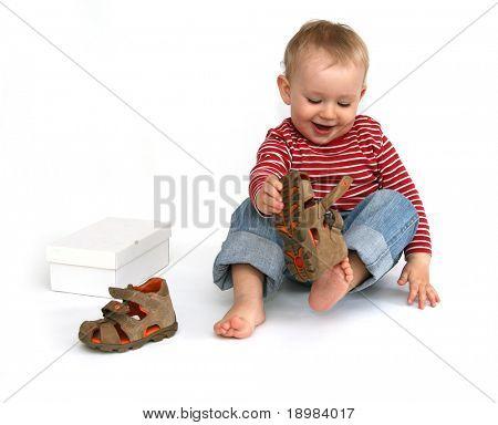 kleines Kind versucht, auf seine Schuhe zu setzen. Baby Boy with Sommerschuhe in der Hand, isoliert auf weiss.