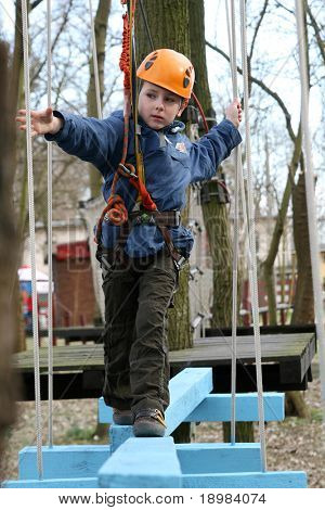 Portrait of 6 years old boy wearing helmet and climbing. Child in a wooden abstacle course in adventure playground
