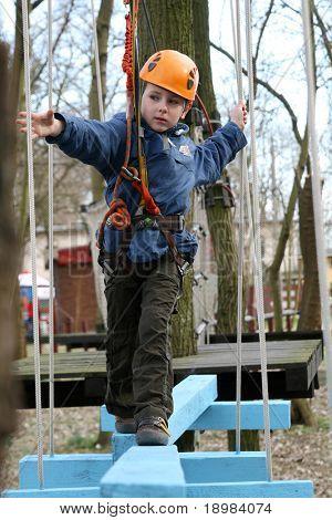 Porträt von 6 Jahre alter Junge trägt Helm und Klettern. Kind in einem hölzernen Abstacle-Kurs in der Adventszeit