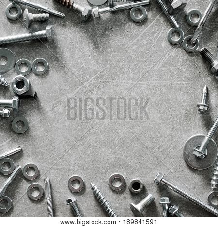 Construction tools. Frame made of screws, nuts and bolts on concrete background. Repair, home improvement concept. Top view, flat lay.