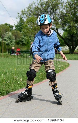 sechs Jahre alte Junge auf Rollerblades fahren lernen. Junge mit Helm und Beschützer.