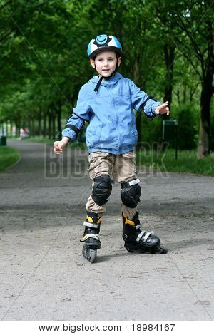 Six years old boy learning to ride on rollerblades. Boy with helmet and protectors.