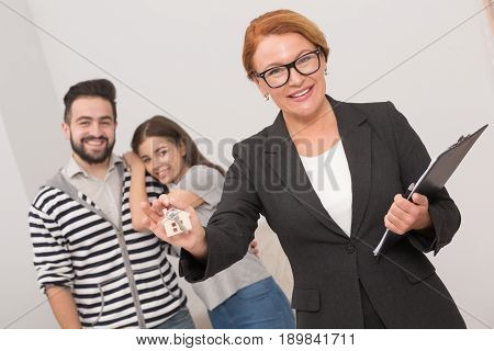 Estate agent is ready to hand over the keys of an apartment to new owners after signing the agreement. Woman agent holding keys in her hand with young couple behind her.