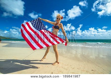 Smiling woman with american flag bikini waving american flag in spectacular tropical Lanikai Beach, east shore of Oahu in Hawaii, USA. Enjoying and freedom in Hawaiian vacations. Patriotic concept.