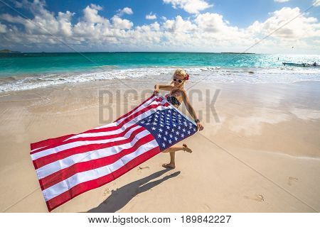 Enjoying woman celebrate independence day waving American flag in tropical Hawaiian beach. Lanikai Beach, east shore of Oahu in Hawaii, USA. Freedom and patriotic concept. Indipendence day.