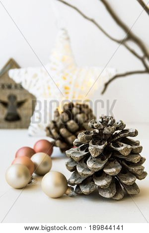White Christmas decoration composition big pine cones scattered baubles shiny star wooden candle holder dry tree branches in background closeup