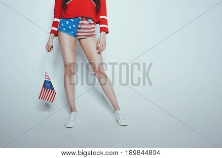 Low section of stylish hipster girl in american patriotic outfit isolated on grey american culture concept