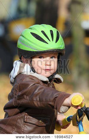 Baby boy in helmet learning to ride on bike