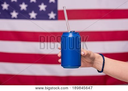 Partial View Of Human Hand Holding Can With American Flag Behind