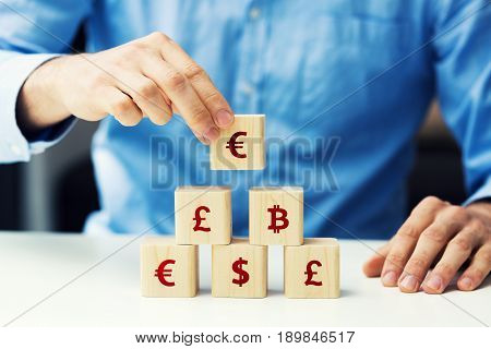 concept of businessman building financial pyramid with wooden blocks
