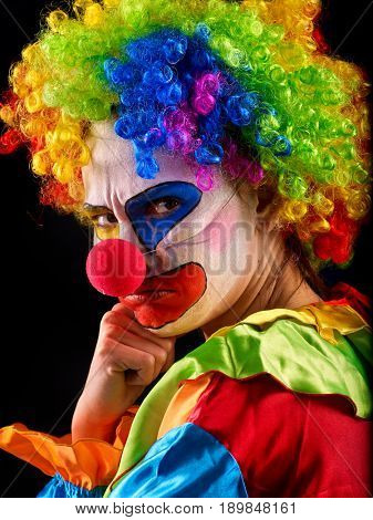 Evil clown on black background. Portrait of mad woman with angry look .